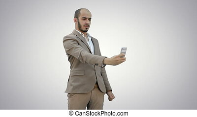 Young businessman taking selfies on phone on white background.
