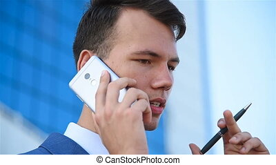 Young Businessman Talking At Cell Phone. Close Up