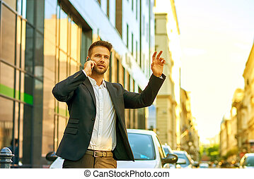 Young businessman talking on a phone and waving for a taxi