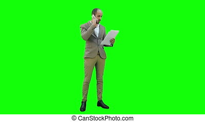 Young businessman talking on cell phone and holding papers on a Green Screen, Chroma Key.