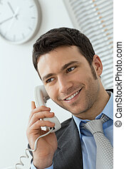 Young businessman talking on landline phone at office, smiling.