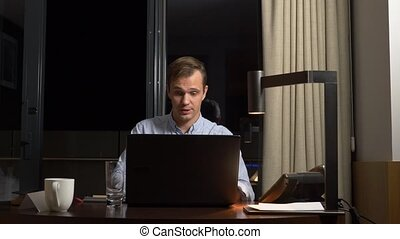 Young businessman talking on landline phone, sitting at desk in office at night. front notebook.