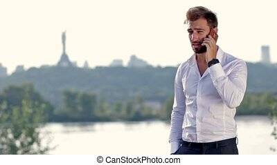 Young businessman talking on mobile phone outdoors