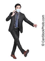 young businessman talking on  mobile phone, walking and wearing a protective medical mask isolated on white background