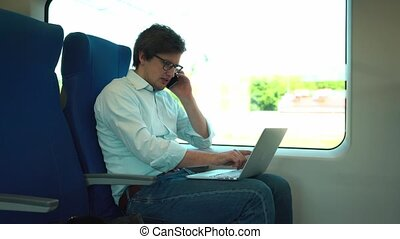 Young businessman talking on phone and using laptop in a train