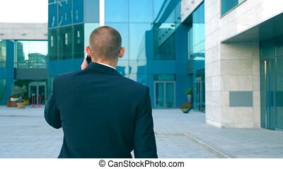 Young businessman talking on phone and walking in street. Unrecognizable man having business conversation during commuting to work. Confident guy in suit being on his way to office building. Back view