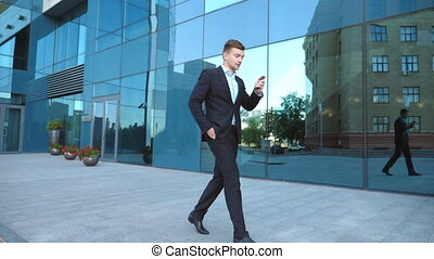 Young businessman talking on phone near office and...