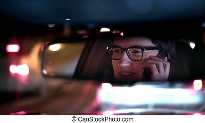 Young businessman talking on phone while in a traffic jam in his car at night