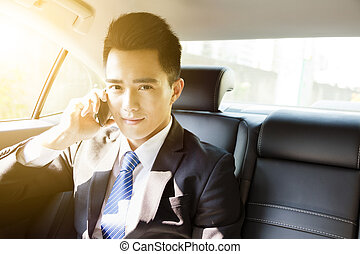 young businessman talking on the phone in car at morning