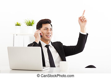 Young businessman talking on the phone in office