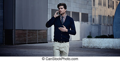Young businessman talking smartphone walking