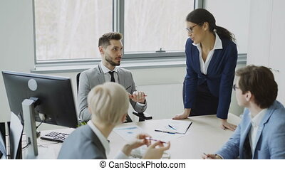 Young businessman talking with male and female colleagues sitting at the table in modern office