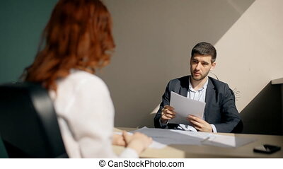 Young businessman talking with woman, holding documents sitting at table in company.