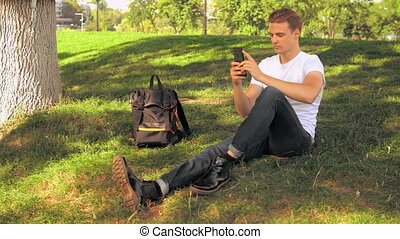 young businessman texting message - student sitting on the...