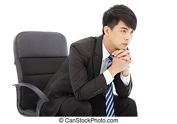 Young businessman thinking and sitting in a chair