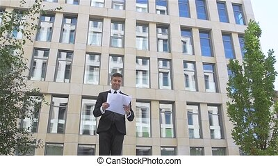 Young businessman throwing paper with arms in the air, slow motion