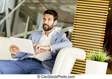 Young businessman touching digital tablet and checking data