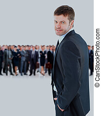 young businessman turned back, looking at the camera and smiling on the background of his team.
