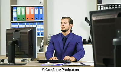 Young Businessman typing on the computer and talking on the phone
