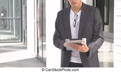 Young businessman uses tablet on background of modern building.
