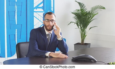 Young businessman uses the phone in the office