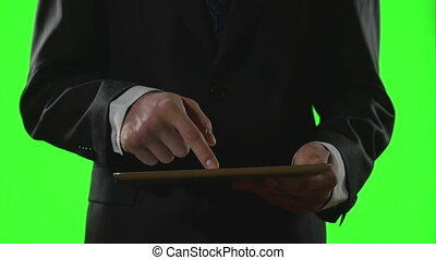 Young businessman using a tablet pc in a virtual business environment on green screen