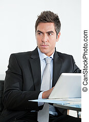 Young Businessman Using Digital Tablet In Office