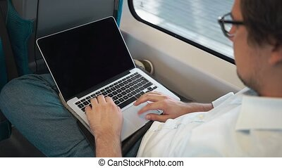 Young businessman using his laptop on his way to work on the train