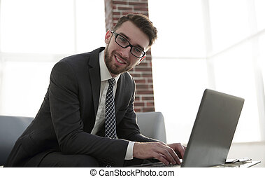 Young businessman using laptop and smiling