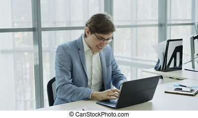 Young businessman using laptop computer receiving good message and become very excited and happy sitting in modern office indoors