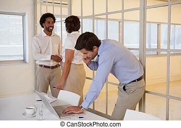 Young businessman using laptop with colleagues shaking hands in background at the office