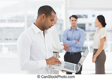 Young businessman using laptop with team behind him