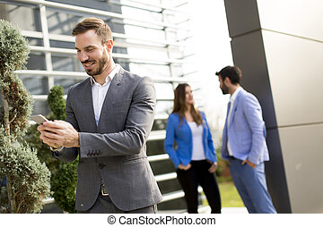 Young businessman using mobile phone outdoor