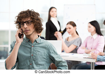 Young businessman using phone in office