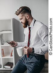 young businessman using smartphone and drinking coffee in office