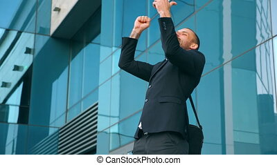 Young businessman using smartphone near office and...