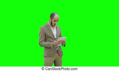 Young businessman using tablet computer on a Green Screen, Chroma Key.