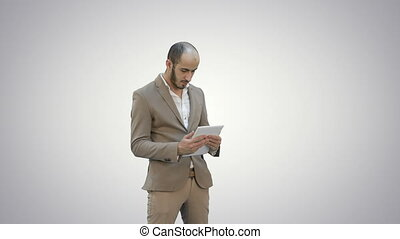 Young businessman using tablet computer on white background.