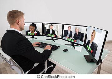 Businessman Video Conferencing On Desk
