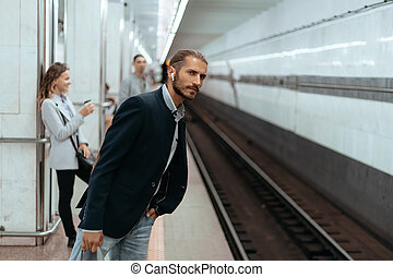 young businessman waiting for a train at subway station.