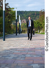 Young businessman walking in a park