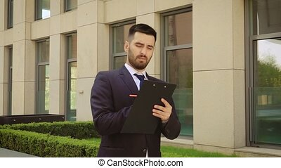 Young businessman walks down the street with a tablet. Close up.