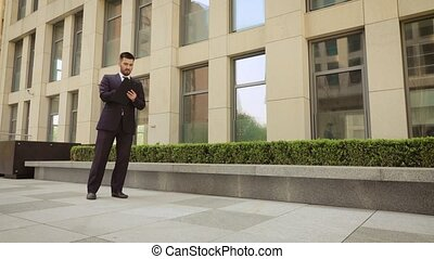 Young businessman walks down the street with a tablet.