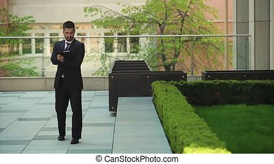 Young businessman walks down the street with a tablet....
