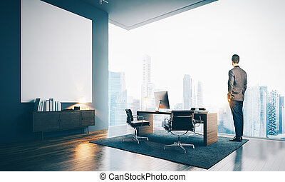 Young businessman wearing modern suit and looking at the city, stands in contemporary office.