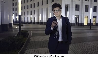 Young businessman web surfing while walking in a night city