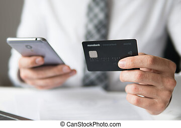 Young businessman with a bank credit card in his hands. Payment of goods online. Smartphone and Internet Commerce. Online trading on the currency exchange. Online payments through the phone.