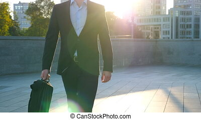 Young businessman with a briefcase walking in city street. Business man commuting to work in the urban environment. Confident guy in suit being on his way to work. Cityscape background. Slow motion