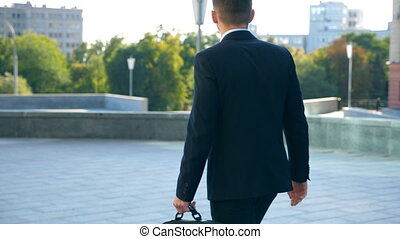Young businessman with a briefcase walking in city street. Unrecognizable business man commuting to work. Confident guy in suit being on his way to job. Cityscape at background. Slow motion Rear view
