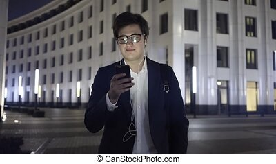 Young businessman with a smartphone and headphones walks in a night city